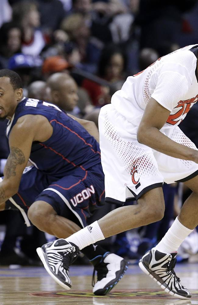 Cincinnati guard Kevin Johnson, right, gets past Connecticut guard Ryan Boatright, left, during the first half of an NCAA college basketball game in the semifinals of the American Athletic Conference tournament Friday, March 14, 2014, in Memphis, Tenn