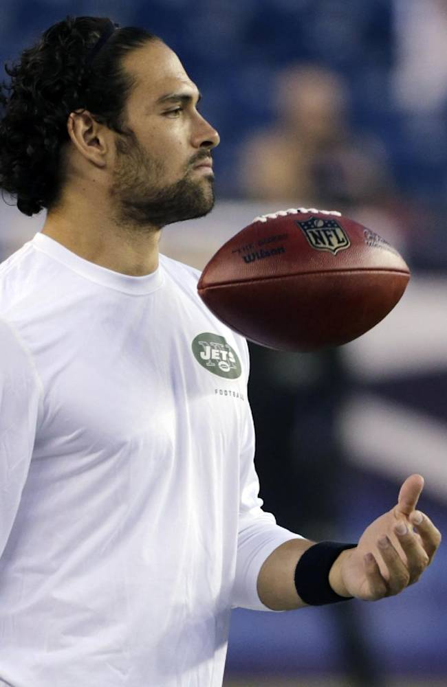 Injured New York Jets quarterback Mark Sanchez, who normally throws right-handed, flips the ball with his left hand before the Jets' NFL football game against the New England Patriots on Thursday, Sept. 12, 2013, in Foxborough, Mass