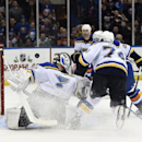 New York Islanders center John Tavares, partly hidden, shoots the puck past St. Louis Blues goalie Martin Brodeur (30) and right wing T.J. Oshie (74) to score in the second period of an NHL hockey game at Nassau Coliseum on Saturday, Dec. 6, 2014, in Unio