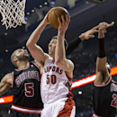 Toronto Raptors' Tyler Hansbrough drives to the net between Chicago Bulls Carlos Boozer (5) and Taj Gibson during the first half of an NBA basketball game, Wednesday, Feb. 19, 2014 in Toronto The Associated Press