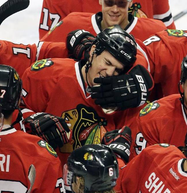 Chicago Blackhawks' Andrew Shaw (65) celebrates with teammates after scoring the game-winning goal during overtime of an NHL preseason hockey game against the Washington Capitals in Chicago, Saturday, Sept. 28, 2013. The Blackhawks won 4-3