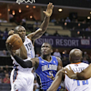 Orlando Magic's Victor Oladipo (5) shoots between Charlotte Bobcats' Bismack Biyombo (0) and Anthony Tolliver (43) during the second half of an NBA basketball game in Charlotte, N.C., Friday, April 4, 2014. The Bobcats won 91-80 The Associated Press