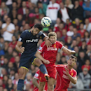 Liverpool's Steven Gerrard, centre right, jumps for the ball against Southampton's Graziano Pelle during their English Premier League soccer match at Anfield Stadium, Liverpool, England, Sunday Aug. 17, 2014