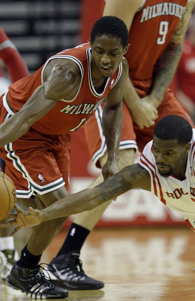 Houston Rockets' Aaron Brooks, right, dives to knock the ball away from Milwaukee Bucks' Brandon Knight (11) during the third quarter of an NBA basketball game, Saturday, Jan. 18, 2014, in Houston. The Rockets won 114-104