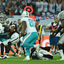 Miami Dolphins' Mike Wallace, left, reaches out to score a touchdown during the NFL football game against Oakland Raiders at Wembley Stadium in London, Sunday, Sept. 28, 2014. The Associated Press