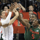 Virginia center Mike Tobey, left, reaches for a rebound as Miami's Davon Reed (5) and Raphael Akpejiori, rear, defend during the first half of an NCAA college basketball game in Charlottesville, Va., Wednesday, Feb. 26, 2014. (AP Photo/Steve Helber)
