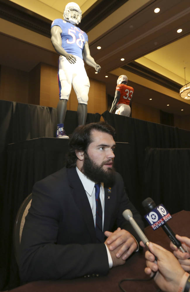Kansas linebacker Ben Heeney speaks to a reporter during the NCAA college Big 12 Conference football media days in Dallas, Monday, July 21, 2014