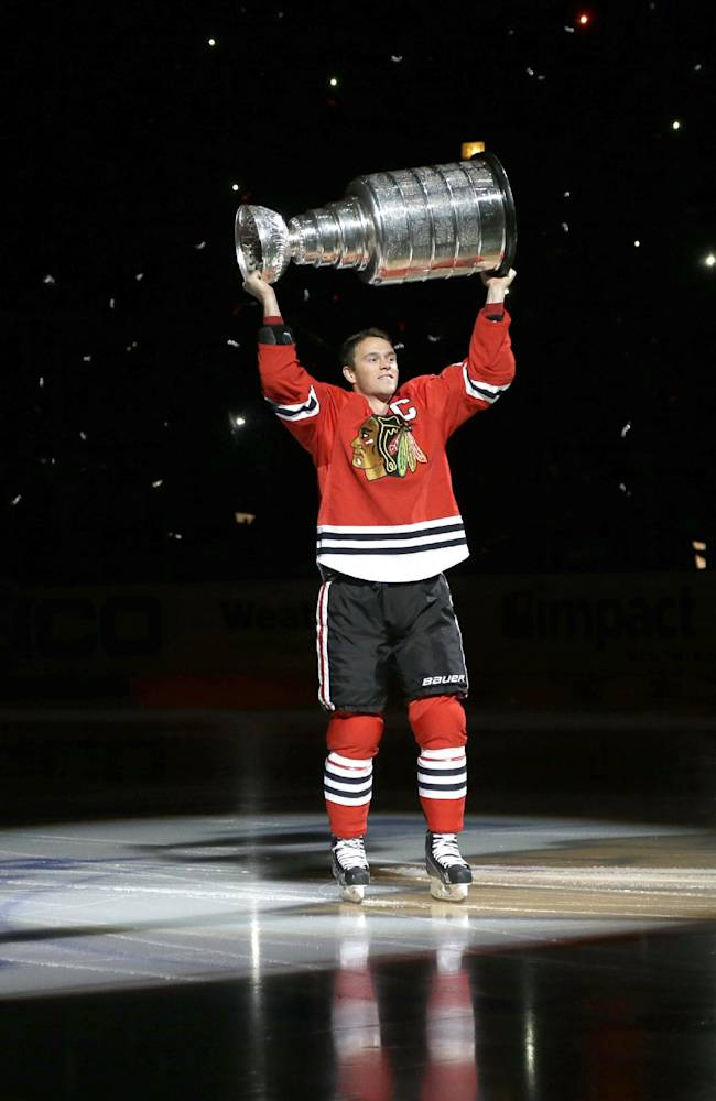 Chicago Blackhawks defenseman Duncan Keith carries out the Stanley Cup during a banner raising ceremony before an NHL hockey game between the Blackhawks and the Washington Capitals, Tuesday, Oct. 1, 2013, in Chicago