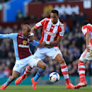 Aston Villa's Fabian Delph, left, takes on Stoke City's Steven Nzonzi, center, and Wilson Palacios during their English Premier League soccer match at Villa Park, Birmingham, England, Sunday, March 23, 2014