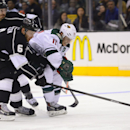 Los Angeles Kings defenseman Jake Muzzin (6) and Los Angeles Kings defenseman Drew Doughty, back left, battle Minnesota Wild left wing Zach Parise (11) for possession during the third period of an NHL hockey game, Monday, March 31, 2014, in Los Angeles. T