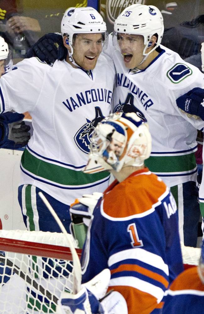 Vancouver Canucks' Yann Sauve (47), Yannick Webber (6), Mike Santorelli (25)  and Dale Weise (32) celebrate a goal as Edmonton Oilers goalie Jason LaBarbera and Denis Grebeshkov (37) look on during first-period preseason NHL hockey game action in Edmonton, Alberta, Saturday, Sept. 21, 2013