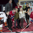 Former Montreal Canadiens captain Saku Koivu, surrounded by family members, drops the puck between Anaheim Ducks' Ryan Getzlaf and Montreal Canadiens' Andrei Markov during a ceremony honoring his career, Thursday, Dec. 18, 2014 in Montreal The Associated