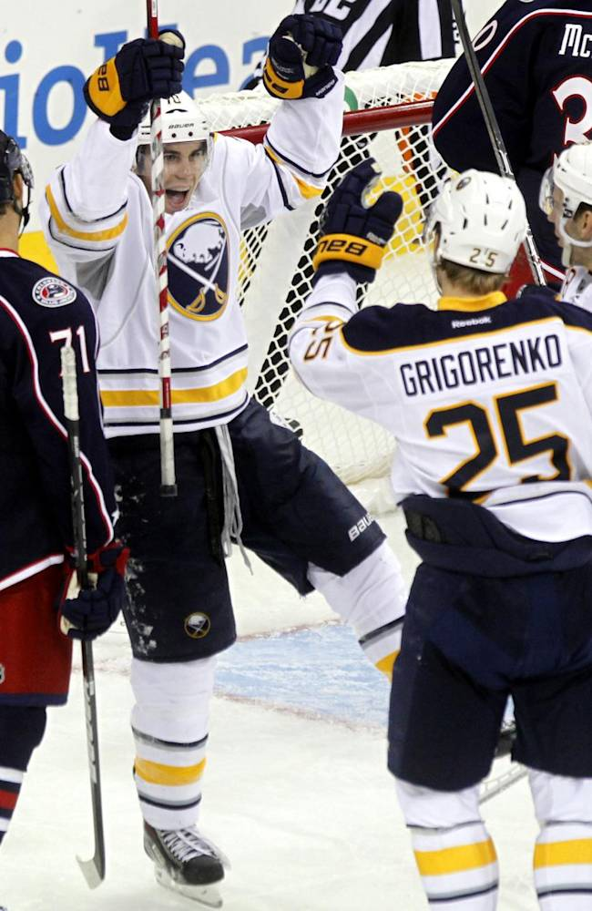 Buffalo Sabres' Corey Tropp, second from left, Mikhail Grigorenko (25), of Russia, and Zemgus Girgensons (28), of Lativa, celebrate Grigorenko's goal in front of Columbus Blue Jackets' Nick Foligno (71) in the third period of a preseason NHL hockey game in Columbus, Ohio, Tuesday, Sept. 17, 2013. The Sabres won 3-1