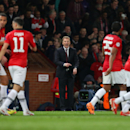 Manchester United's manager David Moyes, center, shouts at his players and points at his watch as they walk back up the pitch for the restart after Robin van Persie scored his side's third goal during their Champions League last 16 second leg soccer match