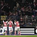 Arsenal's Lukas Podolski, hugged by his teammate Arsenal's Aaron Ramsey, at centre, celebrates after he scored his sides second goal during the Group D Champions League match between Anderlecht and Arsenal at Constant Vanden Stock Stadium in Brussels, Bel