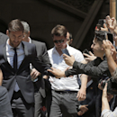Barcelona soccer player Lionel Messi, left, leaves the court in Barcelona, Spain, Thursday, June 2, 2016. Lionel Messi denied having knowledge of the tax issues that led to fraud charges against him, saying Thursday he signed documents without reading the