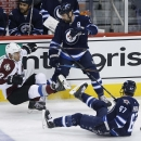 Colorado Avalanche's Jarome Iginla (12), Winnipeg Jets' Mark Stuart (5) and Michael Frolik (67) collide during first-period NHL hockey game action in Winnipeg, Manitoba, Friday, Dec. 5, 2014 The Associated Press