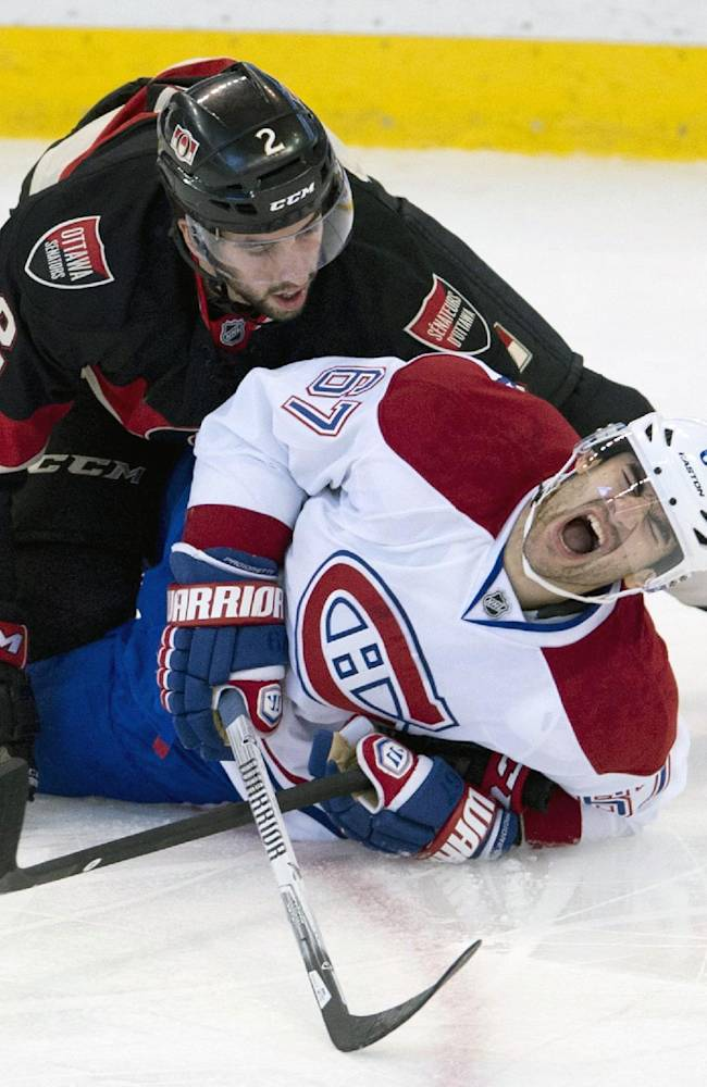 Montreal Canadiens left wing Max Pacioretty reacts as Ottawa Senators defenseman Jared Cowen falls on top of him during the first period of an NHL hockey game, Thursday, Nov. 7, 2013 in Ottawa
