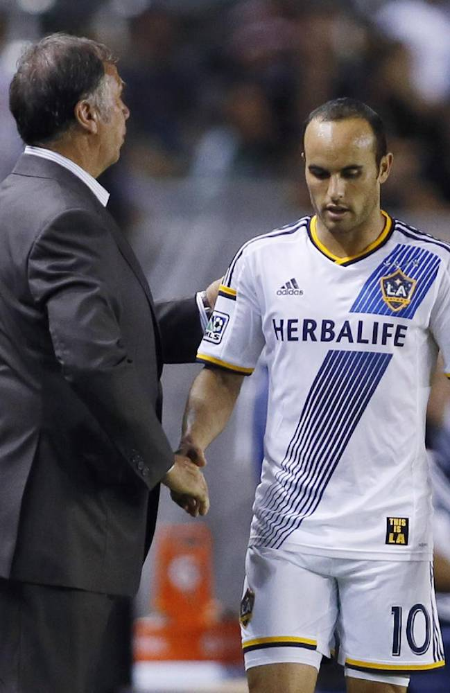 Los Angeles Galaxy's Landon Donovan shakes hands with coach Bruce Arena as he comes out of the MLS soccer game against D.C. United during the second half, Wednesday, Aug. 27, 2014, in Carson, Calif. The Galaxy won 4-1