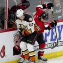 Ottawa Senators defenseman Cody Ceci, right, battles with Anaheim Ducks center Rickard Rakell along the boards for possession of the puck during the second period of an NHL hockey game Friday, Dec. 19, 2014, in Ottawa, Ontario. (AP Photo/The Canadian Press, Adrian Wyld)