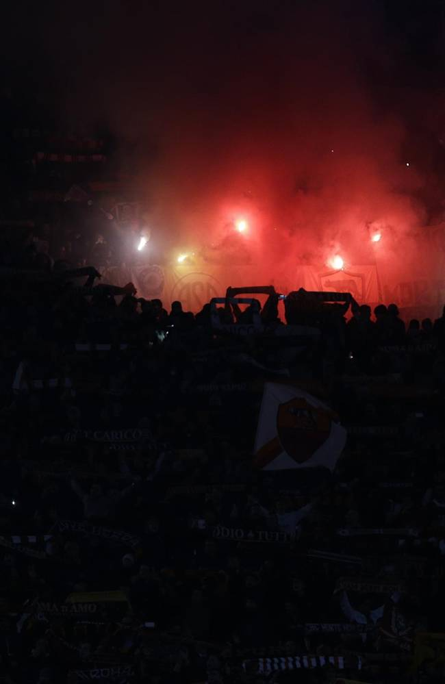 As Roma supporters light flares during an Italian Cup, round of eight, soccer match, between AS Roma and Juventus at Rome's Olympic stadium, Tuesday, Jan. 21, 2014