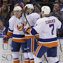 New York Islanders center Ryan Strome, left, celebrates with right wing Colin McDonald and defenseman Matt Carkner, right, after scoring against the Tampa Bay Lightning during the second period of an NHL hockey game Thursday, March 27, 2014, in Tampa, Fla