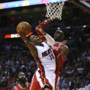 Houston Rockets' Dwight Howard (12) is unable to block Miami Heat's Mario Chalmers (15) during the first half of an NBA basketball game in Miami, Sunday, March 16, 2014 The Associated Press