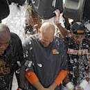 Cleveland Browns nose tackle Phil Taylor, left, head coach Mike Pettine, center, and cornerback Justin Gilbert get ice dumped over them after practice at NFL football training camp in Berea, Ohio Friday, Aug. 15, 2014. The Browns were challenged by the Baltimore Ravens to take the ALS Ice Bucket Challenge, to raise awareness about amyotrophic lateral sclerosis, also known as Lou Gehrig's Disease. (AP Photo/Mark Duncan)