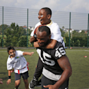 Oakland Raiders Marcel Reece plays football with children during an event at Guildford, England, Tuesday, Sept. 23, 2014. The Raiders will play the Miami Dolphins in an NFL football game at London's Wembley Stadium on Sunday Sept. 28. The Associated Press