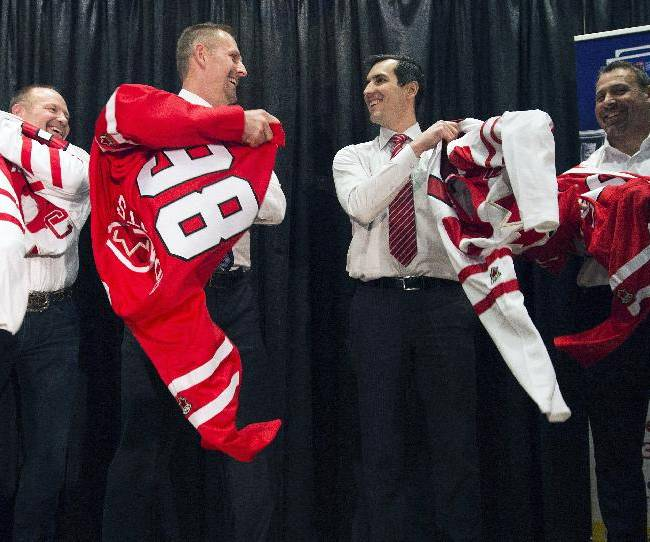 Team Canada honorary captains, from left, Wendel Clark, Gary Roberts, Marc Dennis and Martin Lapointe put on the official Team Canada jersey during the start of world juniors selection camp in Toronto on Friday, Dec. 13, 2013