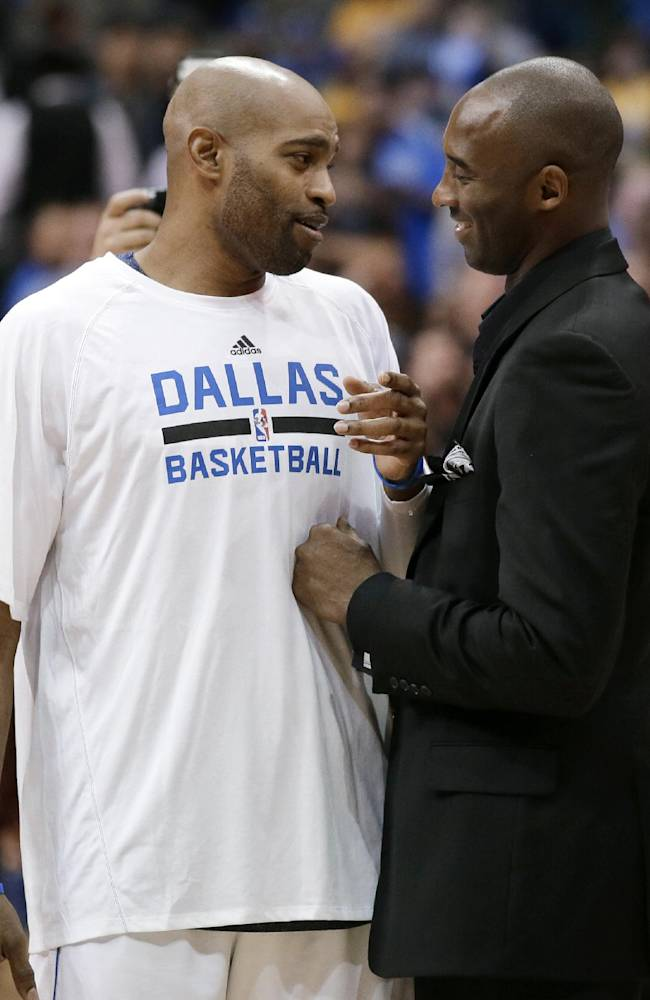 Dallas Mavericks' Vince Carter, left, talks with Los Angeles Lakers' Kobe Bryant, who is out of the lineup due to injury, after an NBA basketball game, Tuesday, Nov. 5, 2013, in Dallas. The Mavericks won 123-104