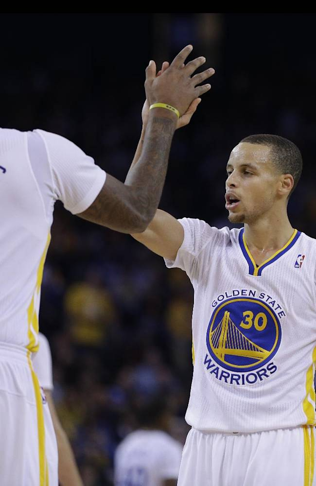 Golden State Warriors' Stephen Curry, right, is congratulated by Marreese Speights after Curry scored against the Los Angeles Lakers during the second half of an NBA basketball game, Saturday, Dec. 21, 2013, in Oakland, Calif