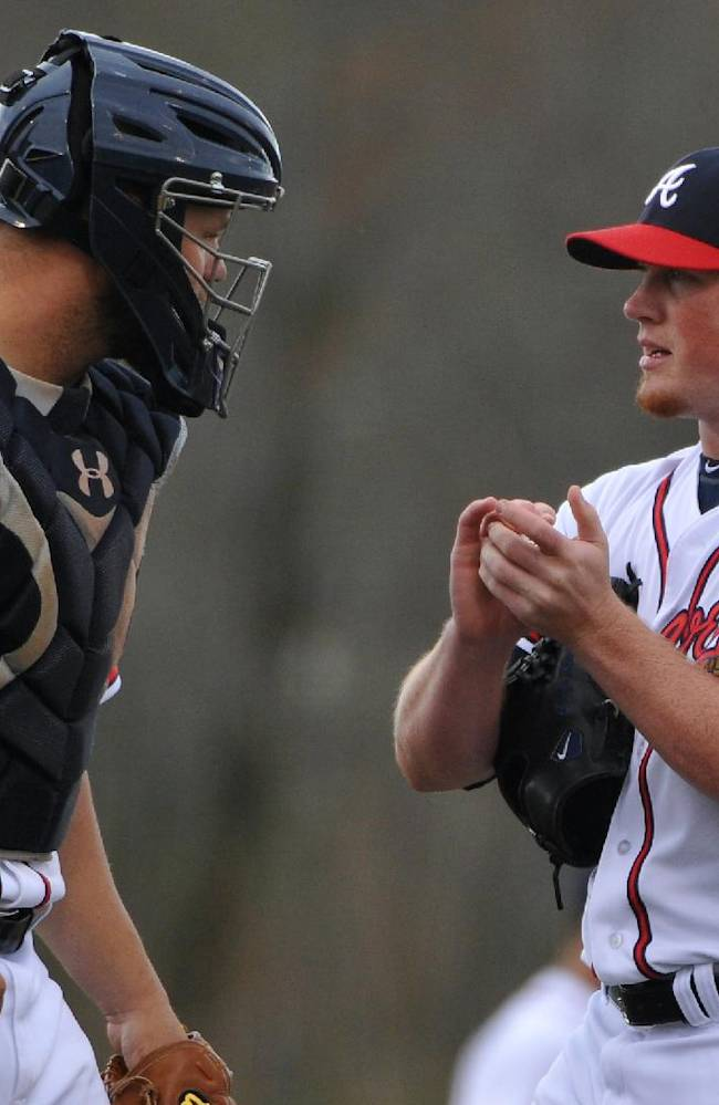 Atlanta Braves pitcher Craig Kimbrell, right, talks to catcher Evan Gattis during the fourth inning of their exhibition baseball game against the team's minor league Future Stars Saturday, March 29, 2014, in Rome, Ga