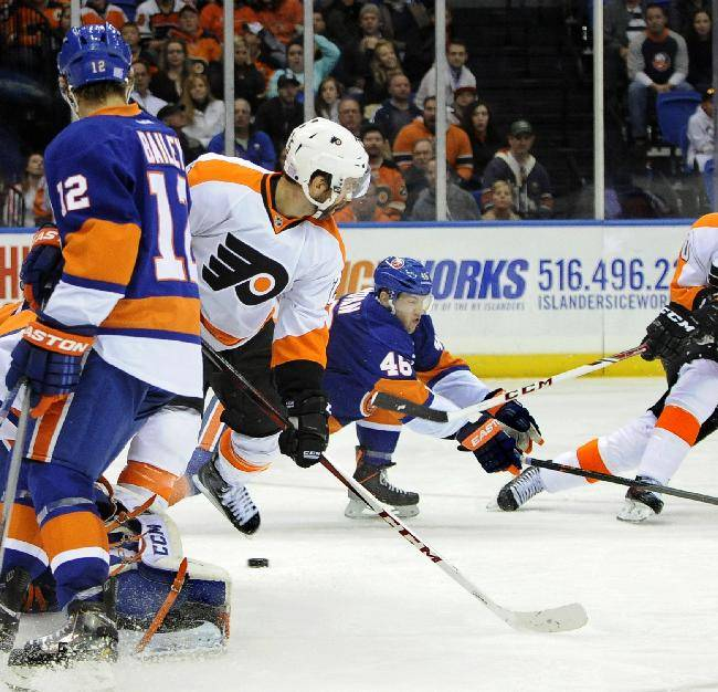 Philadelphia Flyers' Vincent Lecavalier (40) shoots the puck past New York Islanders' Matt Donovan (46), Josh Bailey (12) and goalie Kevin Poulin (60) for a hat trick goal as Philadelphia Flyers center Maxime Talbot (25) stands by in the third period of an NHL hockey game at the Nassau Coliseum on Saturday, Oct. 26, 2013, in Uniondale, N.Y. The Flyers won 5-2