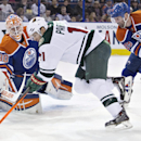 Minnesota Wild's Zach Parise (11) is stopped by Edmonton Oilers goalie Ben Scrivens (30) as Sam Gagner (89) tries to defend during first period NHL hockey action in Edmonton, Canada, Thursday, Feb. 27, 2014 The Associated Press
