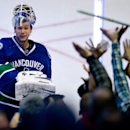 Vancouver Canucks goalie Eddie Lack, of Sweden, tosses his stick into the crowd after shutting out the Carolina Hurricanes 2-0 in an NHL hockey game, in Vancouver, British Columbia, Monday, Dec. 9, 2013 The Associated Press