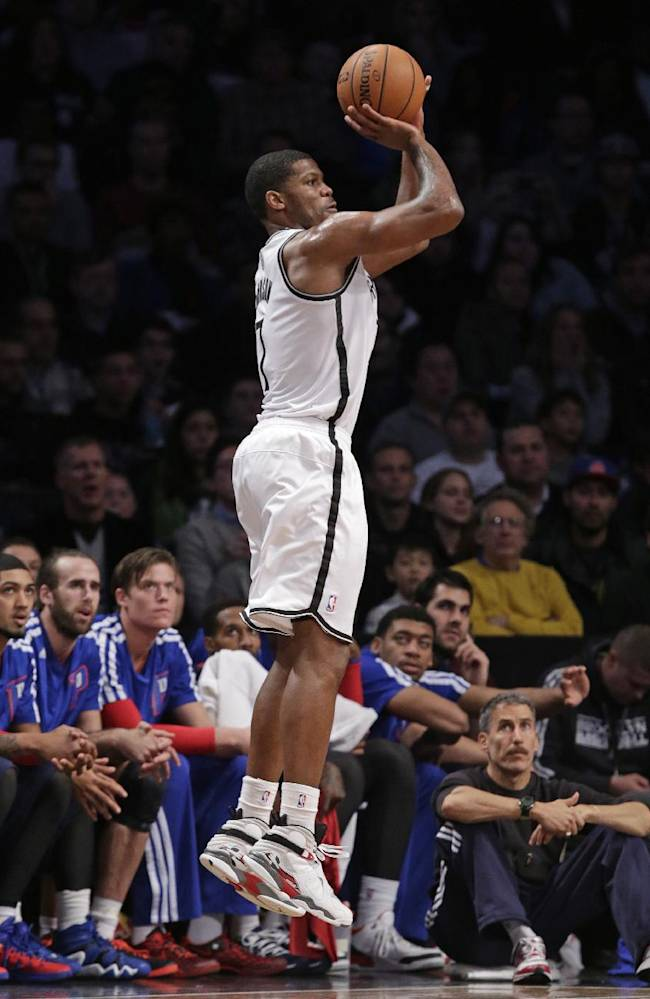 The Detroit Pistons bench looks on as Brooklyn Nets guard Joe Johnson (7) shoots a 3-point shot in the second half of an NBA basketball game, Sunday, Nov. 24, 2013, in New York. The Pistons won 109-97