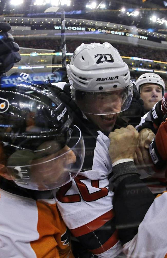 Philadelphia Flyers' Kris Newbury (45), Mark Streit, second from left, of Switzerland, and Zac Rinaldo, left, battle with New Jersey Devils' Ryan Carter (20) during the first period of an NHL hockey game on Thursday, Nov. 7, 2013, in Philadelphia