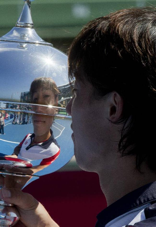 Japan's Kei Nishikori looks at the trophy after his win over Tomas Berdych of the Czech Republic in their final match of the Kooyong Classic ahead of the Australian Open tennis championship in Melbourne, Australia, Saturday, Jan. 11, 2014