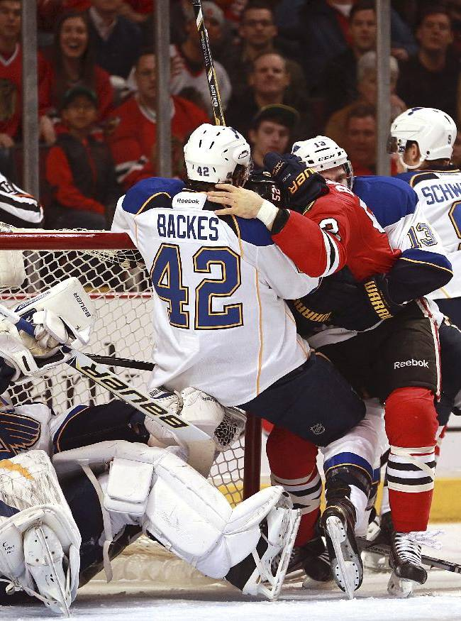 Chicago Blackhawks Brandon Bollig and St Louis Blues' David Backes, second from left, get tangled in front of the Blues goalie Brian Elliot, left, during the first period of an NHL hockey game in Chicago on Sunday, April 6, 2014