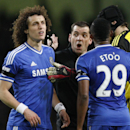 Chelsea's David Luiz, left, is shown a yellow card by referee Phil Dowd, second left during their English FA Cup fifth round soccer match against Manchester City at the Etihad Stadium, Manchester, England, Saturday, Feb. 15, 2014