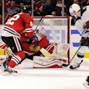 Minnesota Wild's Charlie Coyle (3) scores a goal on Chicago Blackhawks goalie Corey Crawford, center, as Brandon Bollig skates near in the first period of an NHL hockey game in Chicago, Thursday, April 3, 2014 The Associated Press
