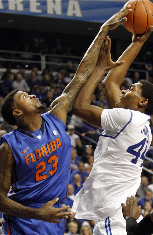 Kentucky's Dakari Johnson, right, shoots as Florida's Chris Walker defends during the first half of an NCAA college basketball game on Saturday, Feb. 15, 2014, in Lexington, Ky