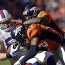 Buffalo Bills tight end Scott Chandler, left, is tackled by Denver Broncos cornerback Aqib Talib, right, and strong safety David Bruton during the first half in an NFL football game Sunday, Dec. 7, 2014, in Denver The Associated Press