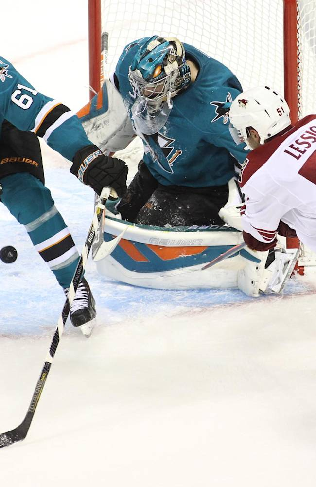 The Sharks' goalie Harri Sateri and Justin Braun (61) defend a shot by the Coyotes' Lucas Lessio in the second period of an NHL preseason hockey game in San Jose, Calif., Saturday, Sept. 21, 2013