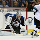 San Jose Sharks center Joe Pavelski, front, fires a shot over the shoulder of Colorado Avalanche goalie Semyon Varlamov, of Russia, for the winning goal in the shootout period of the Sharks' 3-2 shootout victory in an NHL hockey game in Denver on Tuesday,