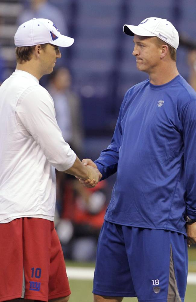 In this Sept. 18, 2010, photo, New York Giants quarterback Eli Manning, left, shakes hands with his brother and Indianapolis Colts quarterback, Peyton Manning, before an NFL football game in Indianapolis. Peyton Manning loves Eli's game, and not just because he's his little brother. The siblings square off Sunday at MetLife Stadium, the third--and quite possibly last--time they'll face each other in the pros. Peyton, now with the Denver Broncos, came out on top in the first two, with his old team, the Colts, beating the Giants in 2006 and `10