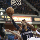 Memphis Grizzlies guard Mike Conley, center, drives to the basket between Sacramento Kings' Greivis Vasquez, , left, of Venezuela and DeMarcus Cousins during the first quarter of an NBA basketball game in Sacramento, Calif., Sunday, Nov. 17, 2013 The Asso
