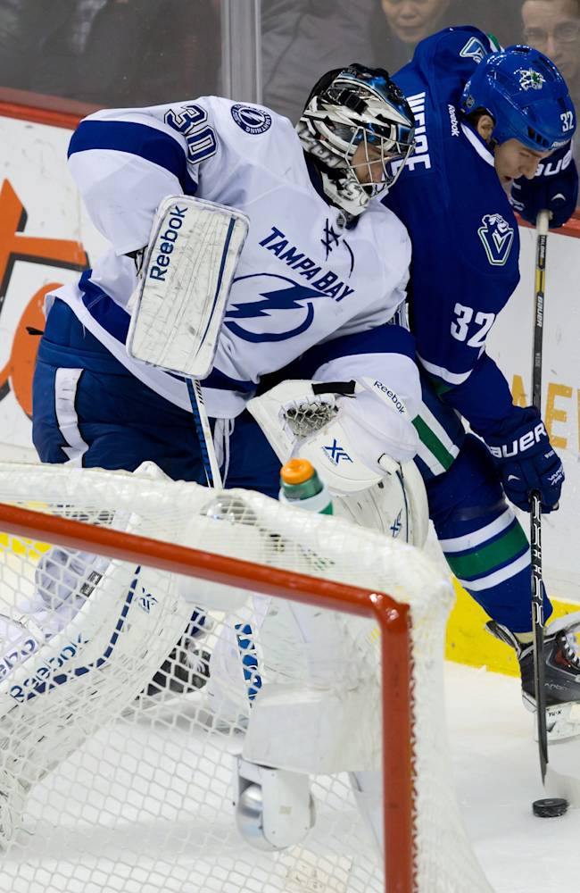Vancouver Canucks' Dale Weise, right, takes the puck away from Tampa Bay Lightning goalie Ben Bishop during an NHL hockey game Wednesday, Jan. 1, 2014, in Vancouver, British Columbia