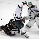 Anaheim Ducks left wing Matt Beleskey (39) gets upended by Minnesota Wild defenseman Jonas Brodin, center, of Sweden, as goalie Josh Harding, right, blocks the shot in the third period of an NHL hockey game Wednesday, Dec. 11, 2013 in Anaheim, Calif. Duck